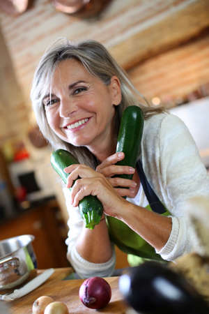 Senior woman in kitchen holding zucchini photo