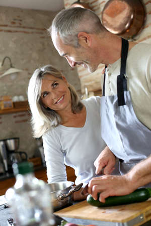 Senior couple in kitchen preparing dinner photo