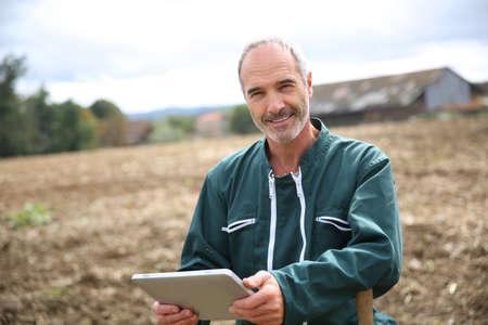 Farmer in field using digital tablet photo