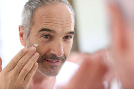 skin treatment: Mature man in front of mirror applying cosmetics