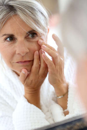 anti wrinkles: Senior woman applying anti-wrinkles cream
