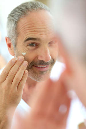 Mature man in front of mirror applying cosmetics Stock Photo - 22417963