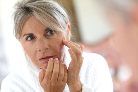 Senior woman applying anti-wrinkles cream  photo