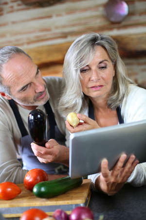Senior couple in home kitchen looking at tablet photo