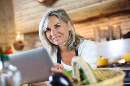 Senior woman cooking with help of recipe on tablet photo