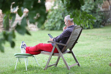 Man relaxing in long chair and using tablet photo