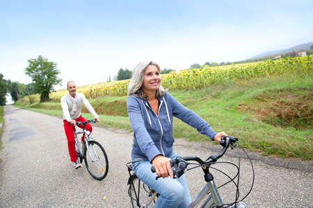 seniors: Senior couple riding bicycle in countryside