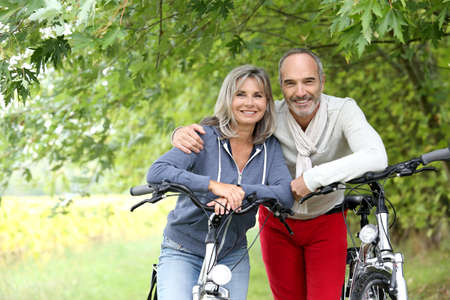 the leisure: Cheerful senior couple with bicycle in country path