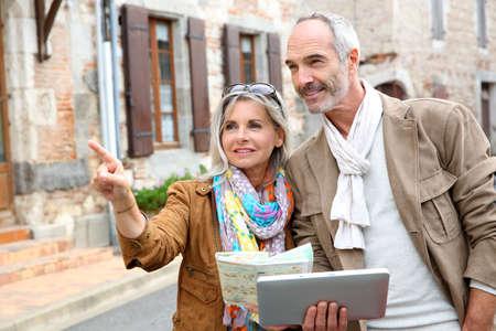 Senior paar een bezoek aan de stad met kaart en tablet