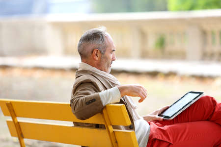 Trendy senior man relaxing on bench with tablet photo