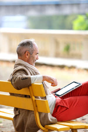 tourist guide: Trendy senior man relaxing on bench with tablet