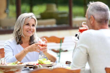 people eating at restaurant: Senior people having lunch in garden
