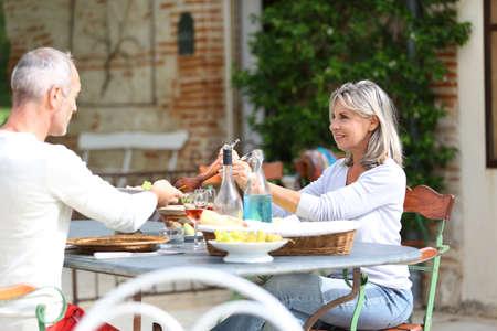 Senior people having lunch in garden photo