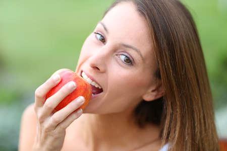 Beautiful girl eating red apple Stock Photo - 22439334