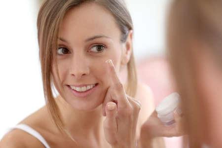 魅力的な女の子が彼女の顔のアンチエイジング クリームを入れて 写真素材
