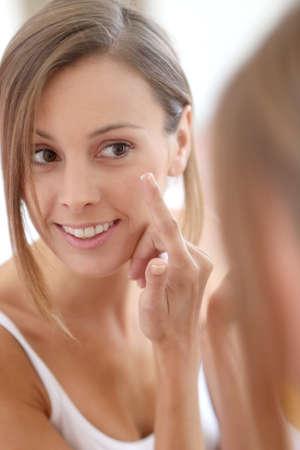 Young woman applying  anti-wrinkles cream Stock Photo - 22439360