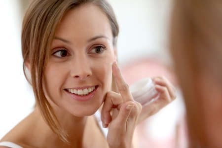 Young woman applying  anti-wrinkles cream Stock Photo - 22439387