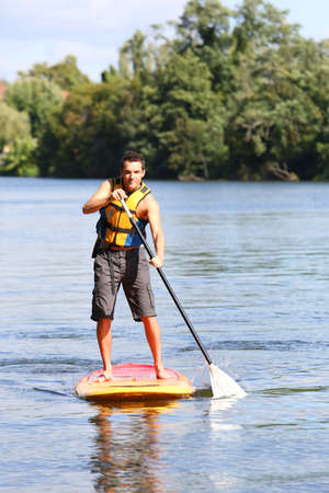 mn: Mn riding stand-up-paddle in river Stock Photo