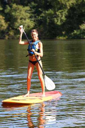 paddling: Woman riding stand-up-paddle on river