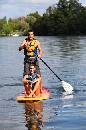 Couple riding stand-up-paddle on river Stock Photo