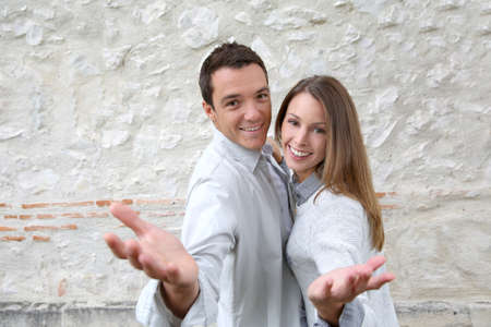 Cheerful couple standing in front of stone wall photo