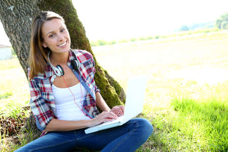 Cheerful girl sitting against tree with laptop photo