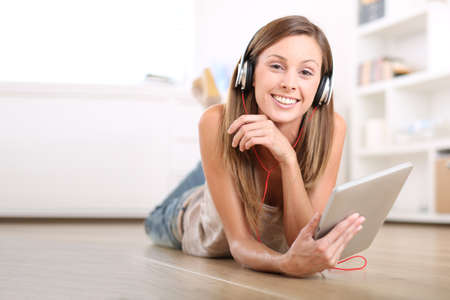 Smiling girl laying on the floor and listening to music photo