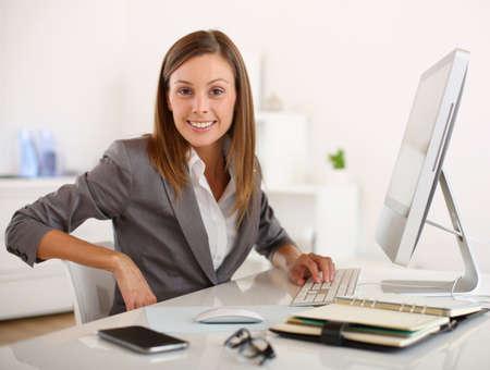 Saleswoman in office working on desktop computer