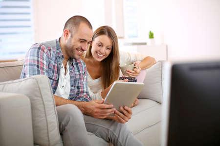 若いカップル自宅でテレビ番組を探してください。