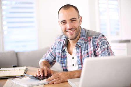 telework: Man working on laptop computer from home