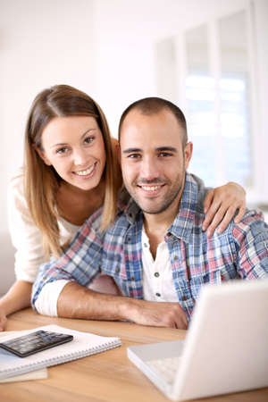 Young cheerful couple calculating savings for home investment photo