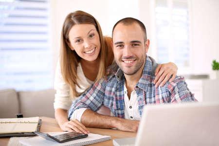 Jonge vrolijke paar het berekenen besparingen voor thuis investering Stockfoto