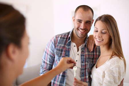 Vrolijk paar krijgt sleutels van hun nieuwe huis Stockfoto