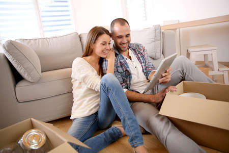 moving box: Young adults using tablet as they are moving in