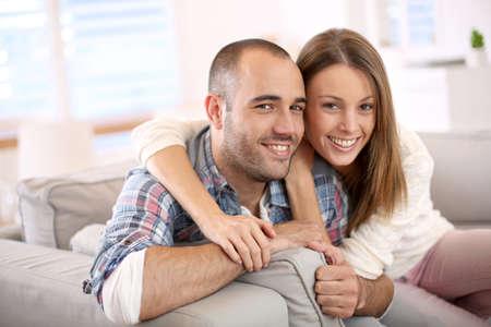 verlobt: Süßes Paar sitzt im Sofa zu Hause Lizenzfreie Bilder