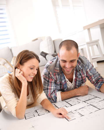 floor plans: Cheerful couple looking at construction house plan  Stock Photo