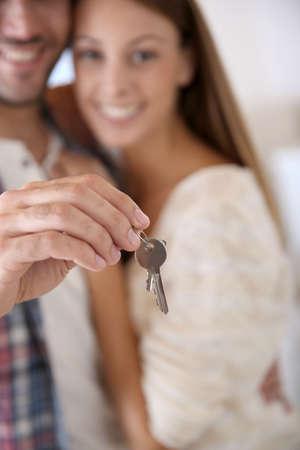 transaction: Close-up van de huissleutel gehouden door jonge man Stockfoto