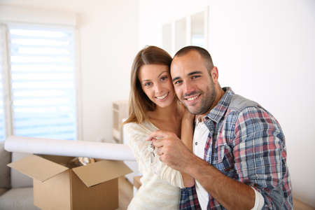buy house: Happy couple in their new home holding key Stock Photo