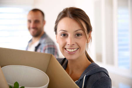 Cheerful young adults packing their stuff in cardboards photo
