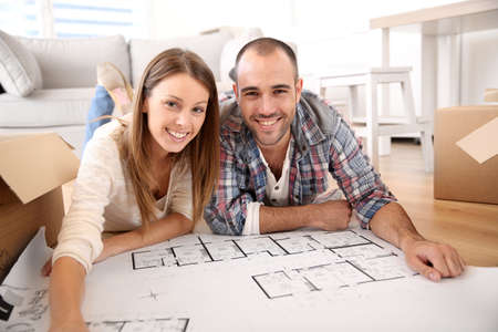 Cheerful couple looking at construction house plan  Stock Photo