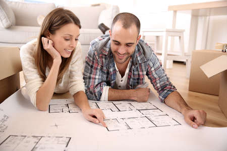 Cheerful couple looking at construction house plan  photo