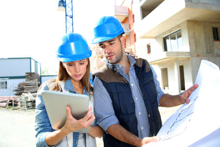 women and men: Construction engineers working together on site
