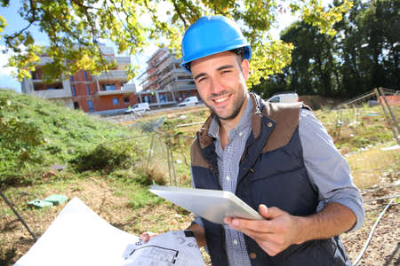 Construction manager using tablet on building site photo