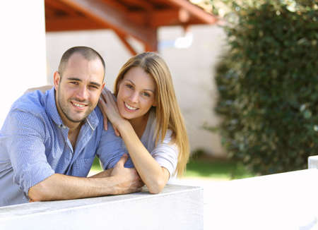 Cheerful couple standing in front of home Stock Photo