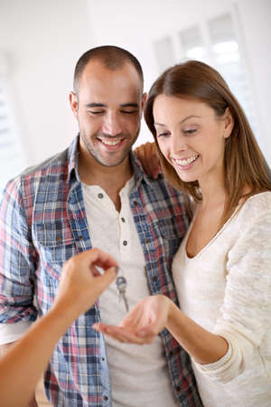 Cheerful couple getting keys of their new home photo