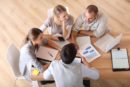 sales team: Upper view of business people around table Stock Photo