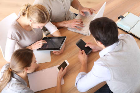 a person: Group of business people using electronic devices at work