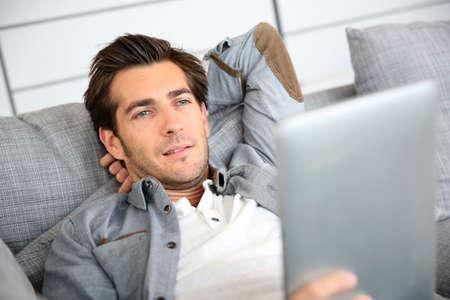 Attraktive Mann zu Hause mit digitalen Tablet