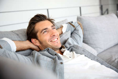 Man relaxing in sofa with arms behind head Imagens