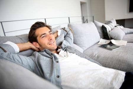 relajado: Hombre que se relaja en el sofá con los brazos detrás de la cabeza Foto de archivo
